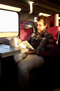 The author on the train through France, reading Elena Ferrante's novel