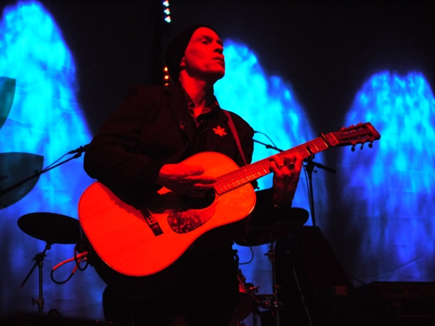 John Mann of Spirit of the West, playing guitar live in a dark image with red glow in the foreground and blue glow in the background
