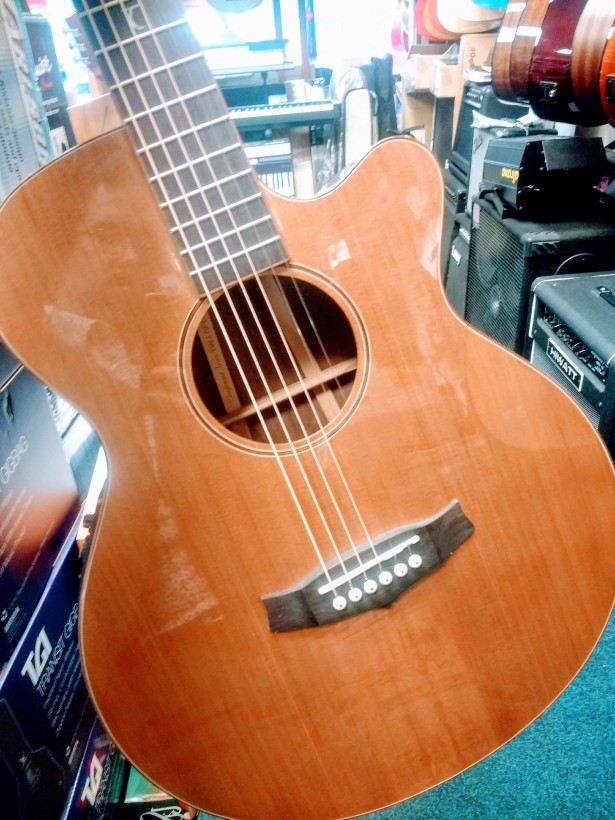 Michael Munnik's reflection in the glossy finish on a cedar-topped Tanglewood acoustic guitar