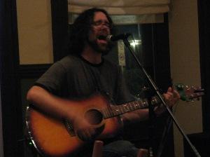 Michael Munnik strumming his guitar and singing at the Branch, Kemptville