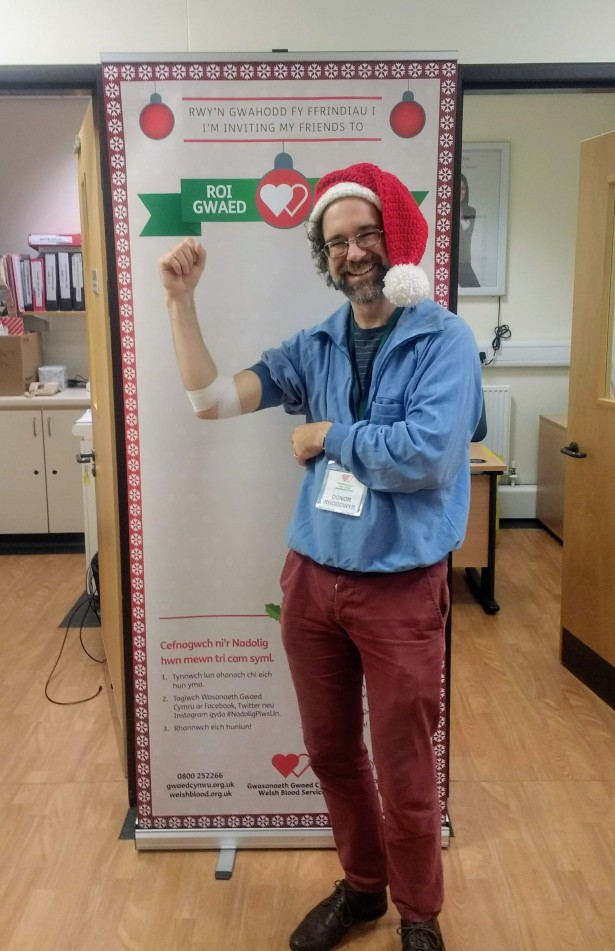 Michael Munnik showing his bandaged arm after a platelets donation, next to a sign encouraging donations at Christmas time